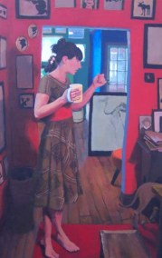Woman in a dress with a mug in a red room full of paintings