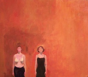 Two women standing in front of an orange wall. One is wearing a dress the second is in her bra and pants