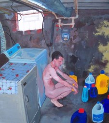 Naked white man squatting ion basement floor next to washing machine