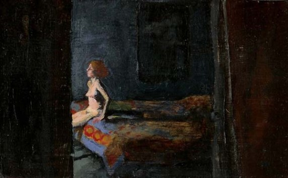 Nude woman on a bed with a quilt in a dark room