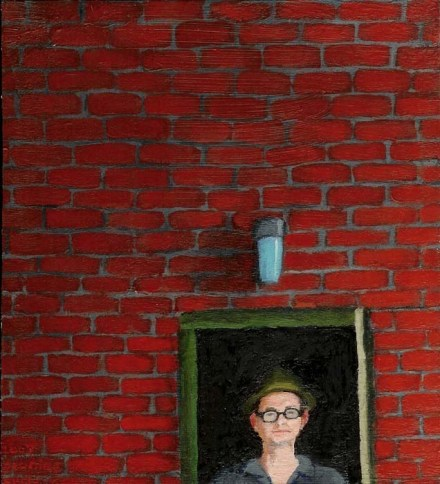 Brick wall with a portrait of a white man with glasses and a hat