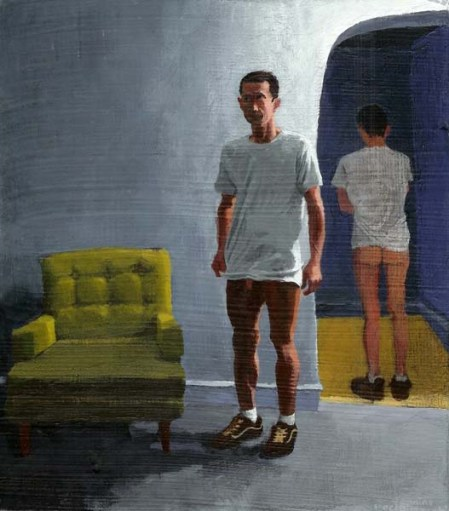 Standing erect man with no pants, a white shirt, and shoes next to agreen chair
