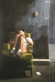 Man lying on a green chair with a white shirt; no pants