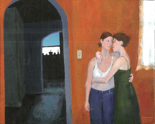 Two women hugging in front of an orange wall