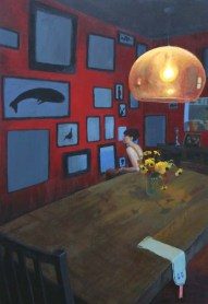 Woman sitting at the end of a table in a red room with paintings